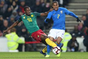 Arnaud Djoum challenges Douglas Costa of Brazil during a friendly last November in Milton Keynes
