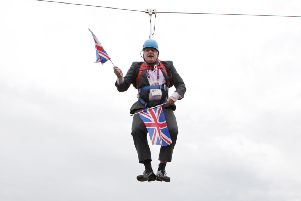 Boris Johnson waves a Union Jack flag while stuck on a zip-wire