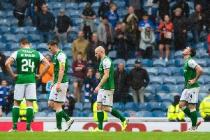 Hibs players hang their heads after the 6-1 thumping at Ibrox. Picture: SNS