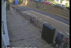 The thief uses bolt cutters to break the bike's lock