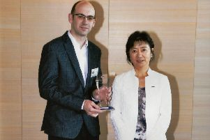 Alex F Noble Nissan sales executive and EV specialist, Alastair Loudon, accepting the EV CEO award from Asako Hoshino, executive vice president and chairwoman of Nissan's Global EV business, at the awards ceremony in Japan.