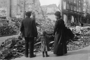 A refugee family returning to Amiens, looking at the ruins of a house, September 17, 1918. � IWM (Q 11341)