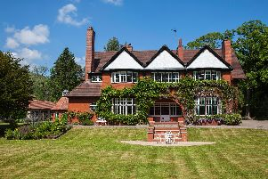 Front view of the home set within beautiful gardens.