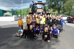 The pupils are pictured with RHET chairman George Lawrie and his tractor, in which he is undertaking a 600-mile trip.