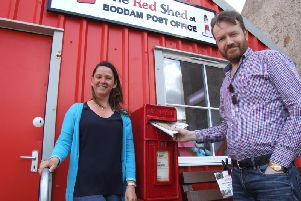 Councillor Stephen Smith makes good use of the new postbox at the Boddam Post Office watched by postmistress Marita Cordiner