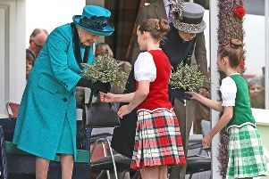 The Queen and Princess Anne are presented with posies by Highland dancers at last year's Gathering