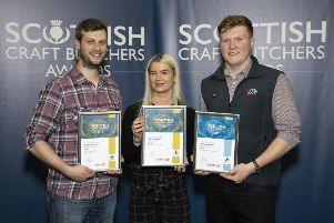 Jason Ward, from John Scott Meats, presents certificates to Euan Sinclair and Adele Stevenson from The Buffalo Farm. Pic: Graeme Hart.