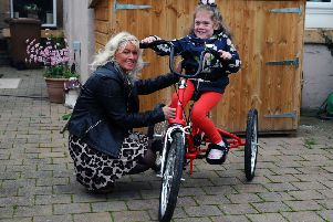 Chiara Petersen Fox is pictured with mum Michelle on her beloved trike. Picture: Michael Gillen