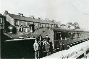 Train and crew at Bonnybridge Railway station. View of station with train at platform with tank engine and carriages.  The crew are by the engine - the driver (Peter Leith) and fireman in light coloured uniform, the guard in dark.  There are also two porters.  There is a tenement in the background.''* COPYRIGHT FALKIRK ARCHIVES. PERMISSION MUST BE SOUGHT BEFORE USE *