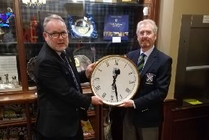 St Andrews Club captain David Edgar receives the clock from Joe Noble, captain of the New Golf Club.