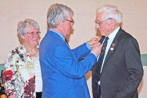 Scottish Curling President Graham Lindsay presenting 50 year medals to Mary Campbell and David Wilson.