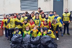 The community-conscious Cub Scouts with the rubbish they removed from the playing fields.