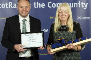 Presenter Angus Thom with Kinghorn artist Lynette Gray as she accepts the award for Outstanding Contribution to Community Rail at the ScotRail in the Community Awards 2019.