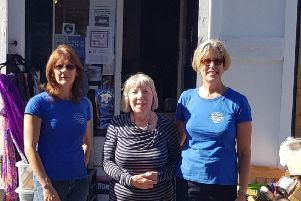 Members of the club pictured with Elizabeth (centre) outside the shop.