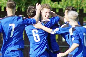 Sandy Strang is congratulated after opening the scoring in the 7-0 win.