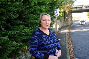 Lesley Weaver near the partially obscured sign at the railway bridge on Windmill Road.  Pic: Fife Photo Agency