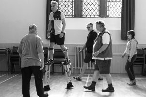 Clark Graham learns to walk on stilts for his part as the Giant in KAOS's production of Big Fish.