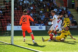 Grant Anderson slides in to score Raith's winning goal in Airdrie. Pic: Fife Photo Agency