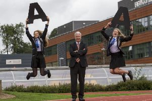 Eastwood High School with pupils Clare Wallace (right) Erin Wallace (left) who achieved multiple As with head teacher Stuart Maxwell