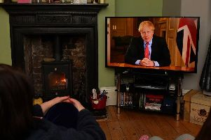 Members of a family listen as Britain's Prime Minister Boris Johnson makes a televised address to the nation from inside 10 Downing Street with the latest instructions to stay at home to help contain the Covid-19 pandemic (Photo: PAUL ELLIS/AFP via Getty Images)