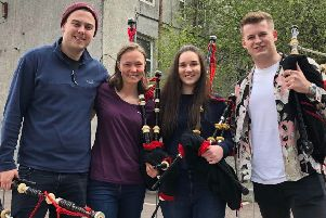 Lathallan senior pupils Lydia Broadley and Rebecca Foster with two members of the Red Hot Chilli Pipers Band