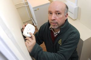 Malcolm Farrow, from OFTEC, checks his carbon monoxide alarm.