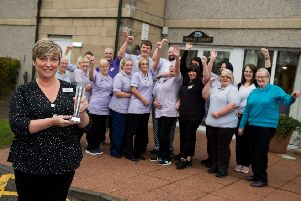 Mowat Court home manager Kirsten Bell shows off the trophy as the staff celebrate their success