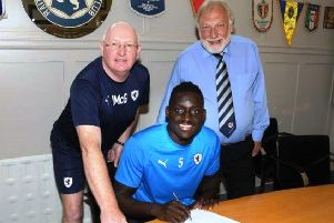 Fernandy Mendy signs for Raith Rovers with manager John McGlynn and chairman Bill Clark (Pic by Tony Fimister)