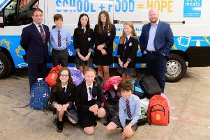 Adam Clark, group business sales and development director at Arnold Clark, and Daniel Adams, executive director of Mary's Meals UK, join pupils supporting to the charity's Backpack Project helping children in Malawi.