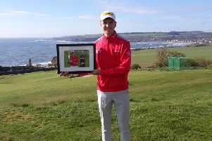 Sam Locke with 18th hole plaque at Stonehaven