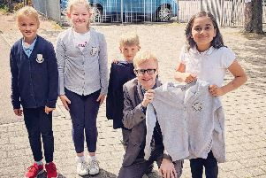 Councillor Leigh Wilson with local pupils promoting the clothing grant