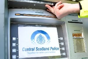 Police doing a credit card skimming demonstration with devices to help warn public of dangers a officer shows where the small video camera would be placed on a cash machine