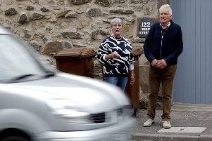 Residents Fiona Gilbert and Ian Strasser next to busy road in Bonnyrigg
