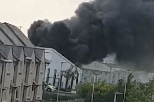 Black smoke billows into the air from the bin store fire at Burnbrae Primary