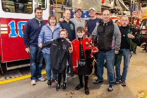Piper Josh Bruce with his personalised jacket from the New York Fire Department (Picture: New York Tartan Week/PA)