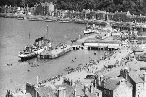 Holidaymakers line the prom as steamers tie up at the pier at Rothesay Bute on the Firth of Clyde.