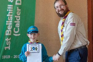 1st Bellshill and Mossend's Group Scout Leader Mark Lunny presents Andrew Megan with a copy of his winning badge design