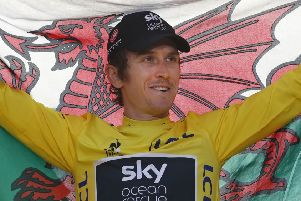 Britain's Geraint Thomas, wearing the overall leader's yellow jersey, holds the Welsh flag on the podium after the twenty-first stage of the Tour de France cycling race over 116 kilometers (72.1 miles) with start in Houilles and finish on Champs-Elysees avenue in Paris, France, Sunday July 29, 2018. (AP Photo/Christophe Ena )
