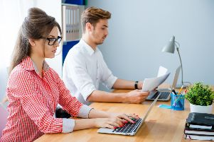 Young business people working at office and typing on laptops