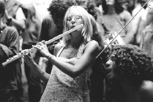 A woman plays a flute at the 1969 Woodstock festival in the US, which inspired countless other similar events around the world (Picture: Granger/Rex/Shutterstock)