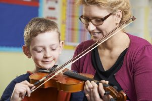 Teacher Helping Pupil To Play Violin In Music Lesson