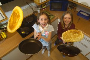 Sisters Emma left, and Joanne Russell, get some pancake-tossing practice in for Shrove Tuesday next week. Picture: Toby Williams