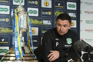 Paul Heckingbottom takes an admiring glance at the Scottish Cup as he briefs the media at Easter Road