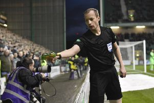 Referee Willie Collum hands over a bottle of 'Buckfast to the police after it was thrown on to the pitch during Hibs' 2-0 defeat by Celtic at Easter Road. Pic: SNS