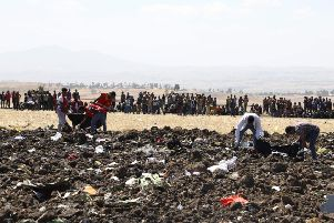 Rescue team collect remains of bodies amid debris at the crash site of Ethiopia Airlines near Bishoftu, a town some 60 kilometres southeast of Addis Ababa, Ethiopia. Picture: MICHAEL TEWELDE/AFP/Getty Images