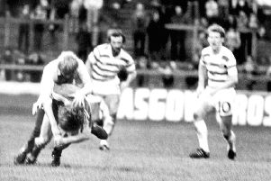 Aberdeen's Gordon Strachan is attacked by a fan who ran on to the pitch during a match against Celtic at Parkhead in November 1980