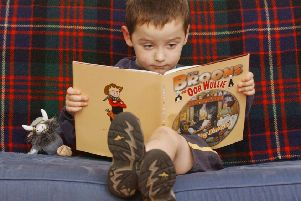 A child reading the Broons and Oor Wullie Annual' Pic: Neil Hanna