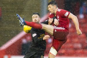 Scott McKenna clears the ball under pressure from Livingston's Ryan Hardie. Picture: SNS Group