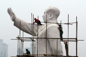 Workers build a scaffold to clean the statue of former Chinese leader Mao Zedong in Chengdu, Sichuan Province. PIC: China Photos/Getty Images