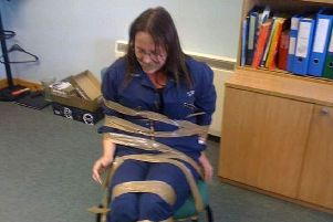 DeeAnn Fitzpatrick complained of a racist and misogynistic culture in a Scottish Government department claims she was taped to a chair and gagged by two male colleagues as a warning to keep quiet